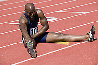 Male sprinter stretching on track