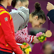 Alexandra Raisman of the United States bent to receive her gold medal in the women's floor exercises apparatus finals at North Greenwich Arena during the 2012 Summer Olympic Games in London, England, Tuesday, August 7, 2012. (David Eulitt/Kansas City Star/MCT)