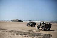 Reenactors driving Willy's jeep on the beach of Aromanche where the remains of the harbour built by the allies are still visible