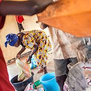 LÉGENDE: Elle verse des grains de riz dans une petite marmite à l'intérieur de bassin. LIEU: Centre COFEMAK, Koumra, Tchad. PERSONNE(S): Responsable du moulin (au centre) des clients (de gauche à droite).