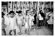 Little girls standing in line giggling, waiting to do an exercise during their ballet lesson. Bethlehem, Palestine, 2007