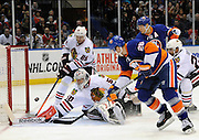 New York Islanders' Thomas Vanek (26) drives the puck past Chicago Blackhawks goalie Corey Crawford (50) to score as Islanders' Kyle Okposo (21) and Blackhawks' Michal Handzus (26) look on during an NHL hockey game at Nassau Coliseum on Thursday, Jan. 2, 2014, in Uniondale, N.Y. (AP Photo/Kathy Kmonicek)