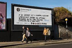 "© Licensed to London News Pictures. 14/02/2019. London, UK.  People walk past a new Jeremy Corbyn billboard from ""Led By Donkeys"" that has been put up in Mr Corbyn's Islington constituency with a message asking for Labour party support on a pubic vote on Brexit. A previous billboard, errected in the same place on Monday was reportedly removed by Islington Council, who later replaced the blank board when challenged. Photo credit: Vickie Flores/LNP"