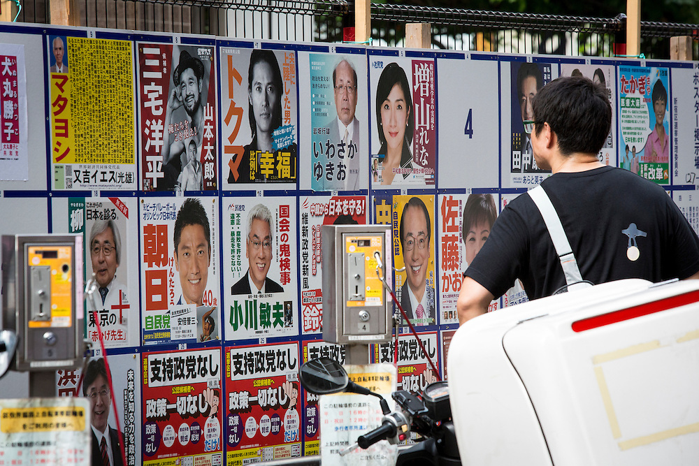 TOKYO, JAPAN - JULY 03 : A man looks at candidates' posters with pictures for the 2016 Upper House election in Tokyo, Japan, on Monday, July 4, 2016. Japanese voters will fill in their ballots next week, July 10, 2016 for the Upper House election. (Photo by Richard Atrero de Guzman/NurPhoto)
