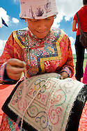 A Mongolian woman dressed in traditional clothing embroiders an Olympic 2008 symbol for a festival contest at a Naadam, Bayan Ul Hot, Inner Mongolia, China.