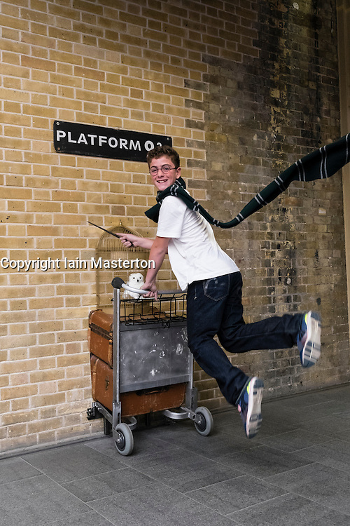 Harry Potter fan jumping at Platform 9 3/4 at King's Cross Station in London United Kingdom