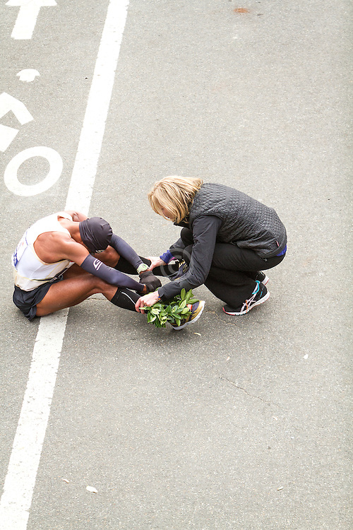ING New York City Marathon: race director Mary Wittenberg checks on Meb Keflezighi as he sits on ground after finishing race