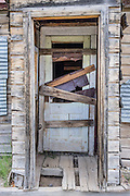 """Ramshackle wood door. Bodie is California's official state gold rush ghost town. Bodie State Historic Park lies in the Bodie Hills east of the Sierra Nevada mountain range in Mono County, near Bridgeport, California, USA. After W. S. Bodey's original gold discovery in 1859, profitable gold ore discoveries in 1876 and 1878 transformed """"Bodie"""" from an isolated mining camp to a Wild West boomtown. By 1879, Bodie had a population of 5000-7000 people with 2000 buildings. At its peak, 65 saloons lined Main Street, which was a mile long. Bodie declined rapidly 1912-1917 and the last mine closed in 1942. Bodie became a National Historic Landmark in 1961 and Bodie State Historic Park in 1962."""