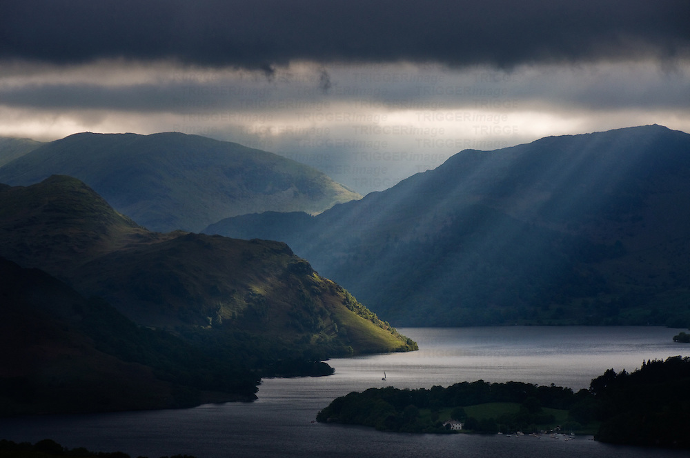 Sunlight shining through dark clouds onto mountains and a lake in England