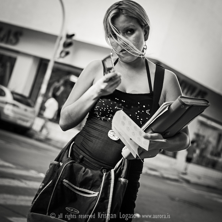 Young business woman walking in the streets of Veracruz wiht briefcase in one hand and the smart phone in other