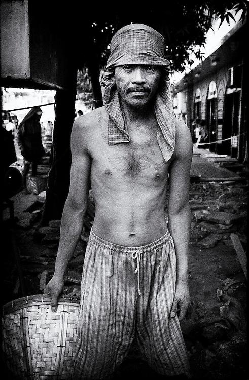 Member of a work crew repairing a sidewalk in the city centre. Yangon (Rangoon) Myanmar (Burma) January 2012