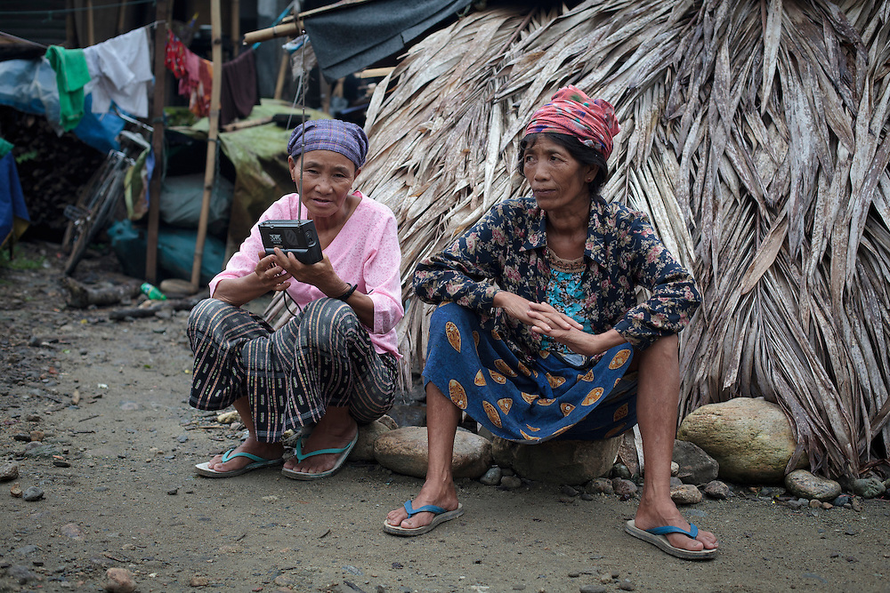 Two Kachin women listen the radio in Woi Chyai Internal Displacement People refugee camp in Laiza village close to the China border, Myanmar on July 16, 2012. According to KIO (Kachin Independence Organization) sources around 50000 Kachin people live as refugees in those camps.