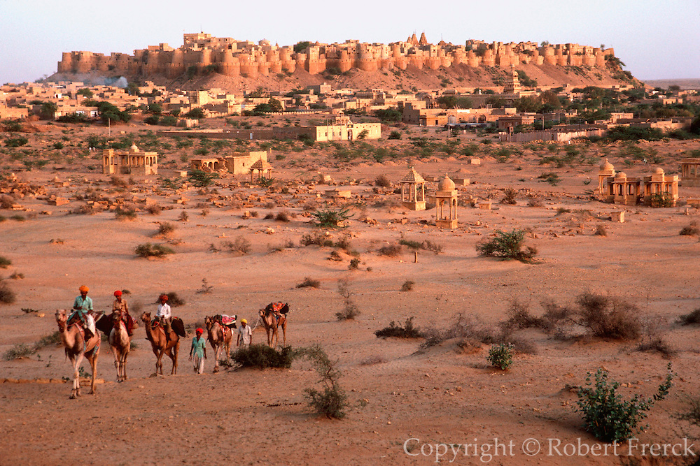 INDIA, RAJASTHAN camel caravan leaving the 11th century city of Jaisalmer in the Great Thar Desert at dusk