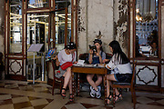 Three Asian girls plan their tour of Venice inside the covered Procuratie Nuovo in Piazza San Marco, Venice, Italy.