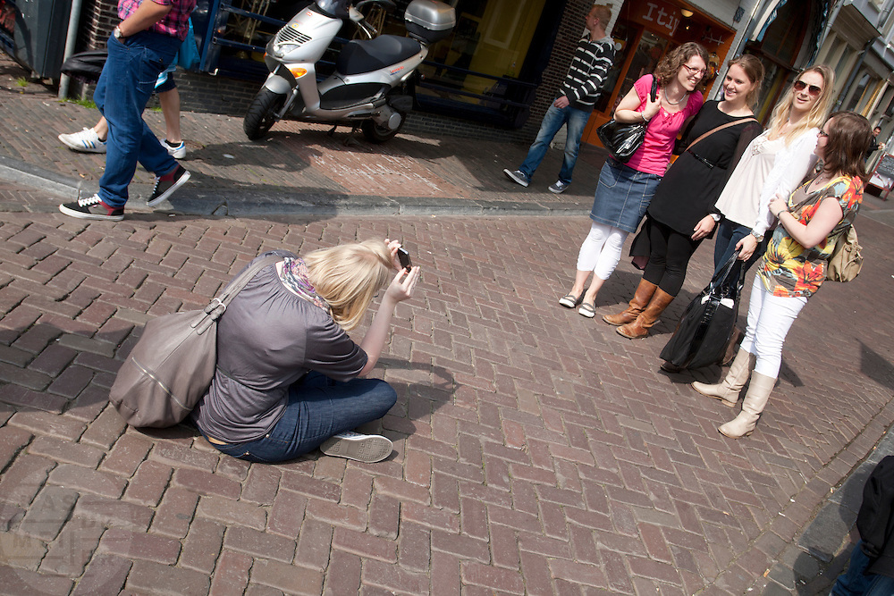 Een meisje zit op de grond om met de iPhone haar vier vriendinnen te fotograferen met de Dom op de achtergrond.<br />