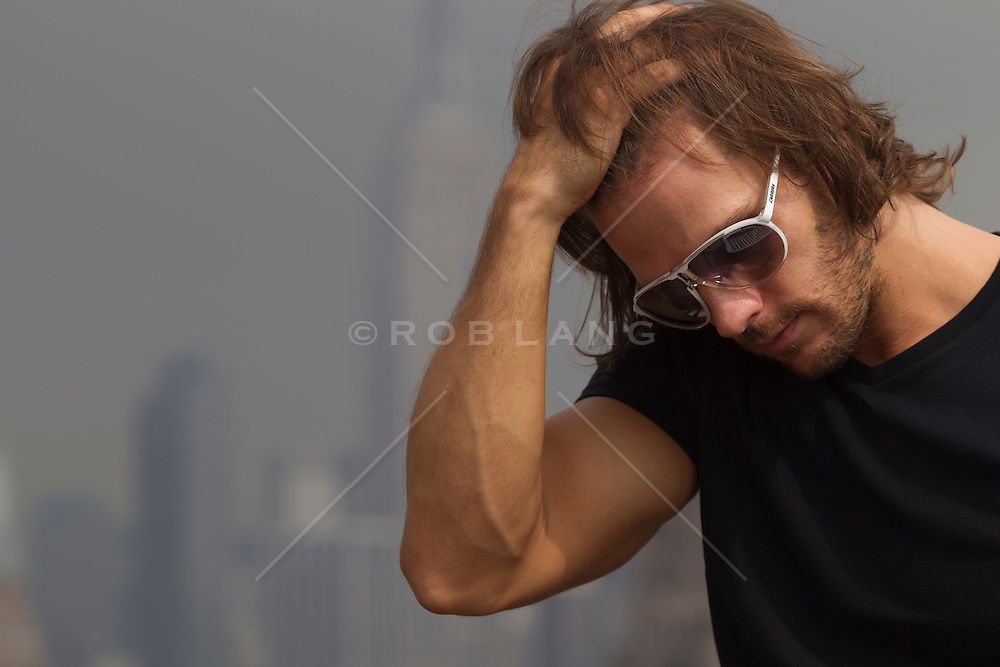 man with long hair and sunglasses with his hand in his hair in New York City