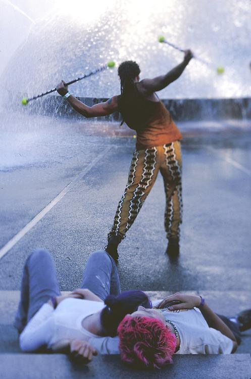 North America, United States, Washington, Seattle, teen couple watching baton twirler at International Fountain in Seattle Center during annual Bumbershoot festival