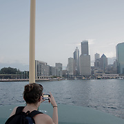 Girl taking a picture of the cityscape. Sydney Bay during sunset seen from a ferry.