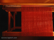 A weaving loom with red yarn.