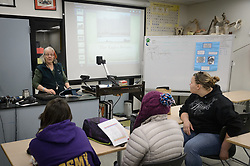 Pam Randles, Takshanuk Watershed Council Education Director, reviews the structure for an upcoming presentation by students who are conducting a weekly count of bald eagles as part of their citizen science project at the Haines School. Students pictured are (left to right) Allison Stuart, Heidi Kattenhorn, and Maggie Martin. The project is part of a field-based for-credit class, sponsored by the Takshanuk Watershed Council, in which students participate in research studies and learn about field data collection. Under the guidance of Pam Randles, Takshanuk Watershed Council Education Director, students count bald eagles in the Chilkat River Valley using spotting scopes at 10 locations and present their data at the Bald Eagle Festival held in November in Haines. During late fall, bald eagles congregate along the Chilkat River to feed on salmon. This gathering of bald eagles in the Alaska Chilkat Bald Eagle Preserve is believed to be one of the largest gatherings of bald eagles in the world.
