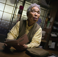 Kuniyoshi Sato, 86 years old, holds his 'atom bomb survivor' documentation, in his home on Amakusa Island, near Nagasaki, Japan, on Wednesday May 25th 2005. Sato was in Hiroshima on the day of the first atomic bombing, 6th Aug. 1945, and also in Nagasaki three days later on the day of the second atomic bombing of Japan by US Military. Nagasaki, Japan.