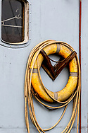 Yellow lifesaver hanging on the outdoor wall of a boat, showing the small window to the Captains area, with a white plastic hanger in the window
