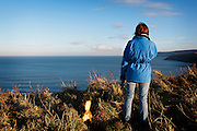 Berwickshire Coastal Path, Copath Cove, middle-aged woman wearing blue jacket and jeans looks out to see on grassy hill with brown dog by her side.