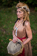 "Oct. 12, 2013. Cynthia Turrentine, known to the pagan community as ""Elf,"" poses with her drum and fox headdress at Wisteria, a private campground that holds festivals and pagan gatherings throughout the summer and fall in Southeast Ohio. Cynthia, a landscaper and stone worker by trade, considers herself a shaman and spiritual healer. She says the fox is her guide in the spirit world."