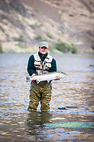 Flyfisherman about to release a wild steelhead along the Deschutes River in eastern Oregon.