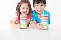 Boy and girl (5-6) sitting at table holding colourful glasses portrait