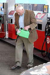 © Licensed to London News Pictures. 29/03/2012. Orpington, UK. A man filling a jerry can withn petrol at a petrol station in Orpington, South London on March 29, 2012. Photo credit : Grant Falvey/LNP