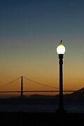 The Golden Gate Bridge at sunset with a lamp post in the foreground.