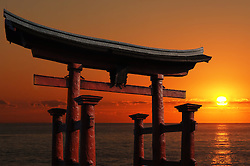 Japanese Temple Gate to Miyajima Shrine looking out over the ocean against a blazing red sunset