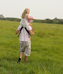 Father carrying his daughter on his shoulders through a grassy field in East Hampton, New York