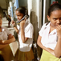 Girls take turns talking on a pay phone after school in Havana.