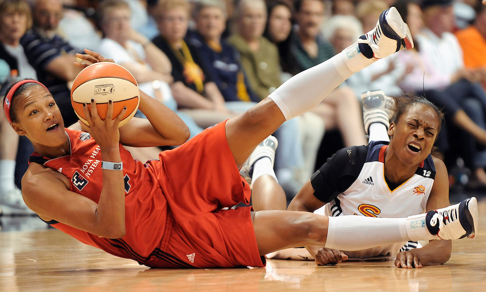 Washington Mystics' Marissa Coleman, left, and Connecticut Sun's Danielle McCray, back both fall to the court during the first half of a WNBA basketball game in Uncasville, Conn., on Saturday, June 4, 2011. (AP Photo/Jessica Hill)