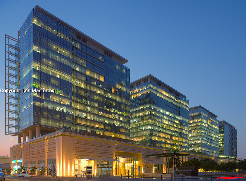 Night view of modern office buildings at night at Jebel Ali Downtown commercial property development in Dubai United Arab Emirates