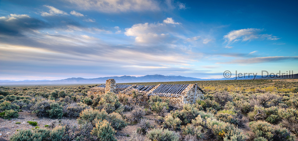 The ruin of an ancient stone ranch house is overgrown by sage brush in Antelope Valley, Nevada.