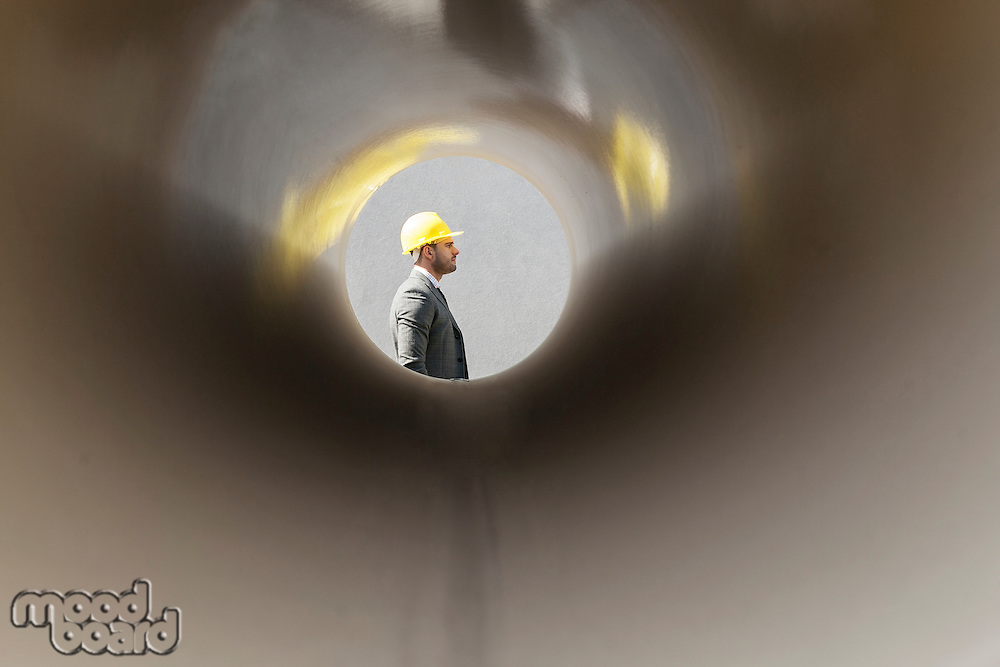Side view of young male architect through large pipe at construction site