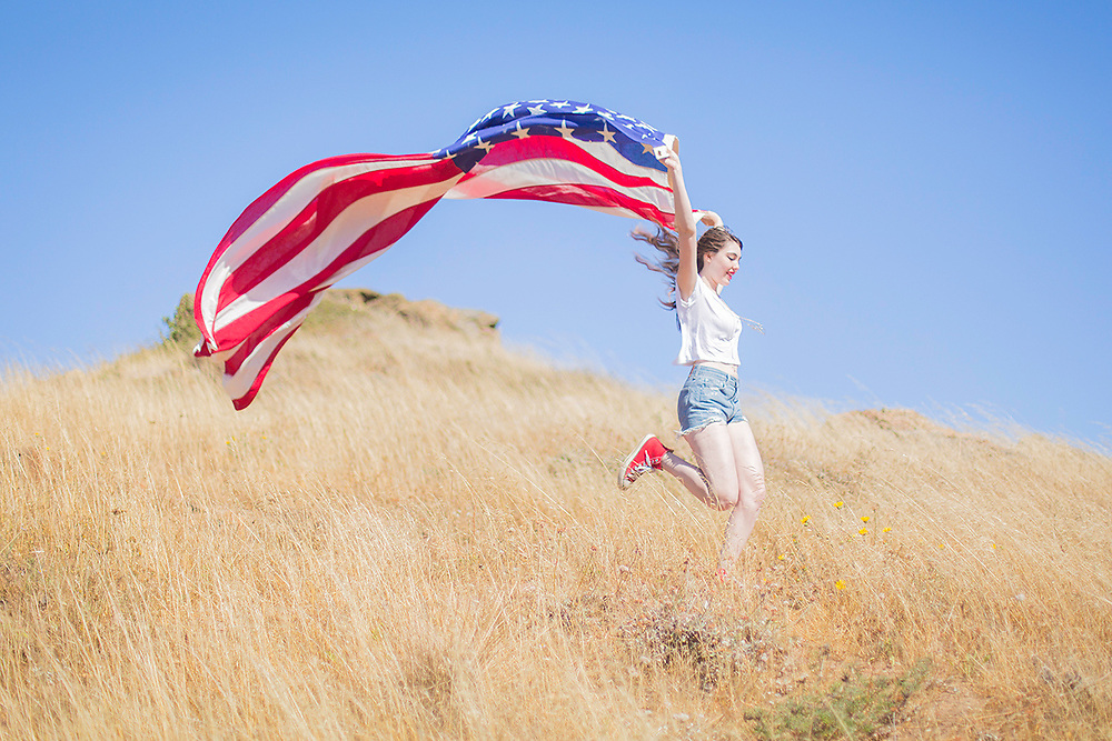 This image is from a series that illustrates young women exploring freedom and power, igniting enthusiasm in beautiful landscapes with patriotic feels.