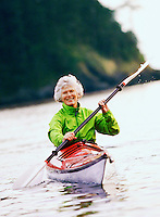 Active woman out paddling a kayak. Deception Pass State Park, WA.