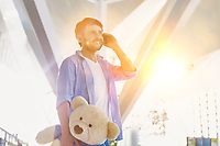 Portrait of man talking on smartphone while holding a teddy bear present for his daughter in airport