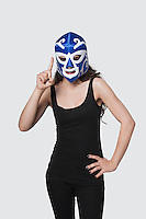 Young female wearing wrestling mask as she raises index finger against gray background
