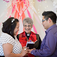 021414  Adron Gardner/Independent<br /> <br /> Minister Linda Rounds-Nichols, center, looks on as Nizhoni Long, left, and Darren Skeet exchange marital vows for a Valentines day Wedding at the McKinley County Courthouse in Gallup Friday.