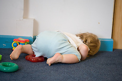 Baby at Nursery School; lying on the floor,