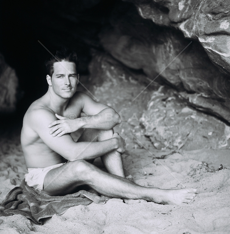 Man in a bathing suit sitting on sand inside cave
