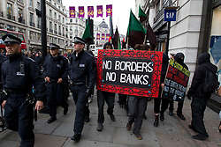 © Licensed to London News Pictures. 11/06/2013. London, UK. Anti-capitalist protesters are seen marching beside police on Regents Street in London today (11/06/2013). The the small demonstration, part of an organised anti-capitalist protest in central London, were time to coincide with the G8 meeting of world leaders in Northern Ireland this week. Photo credit: Matt Cetti-Roberts/LNP