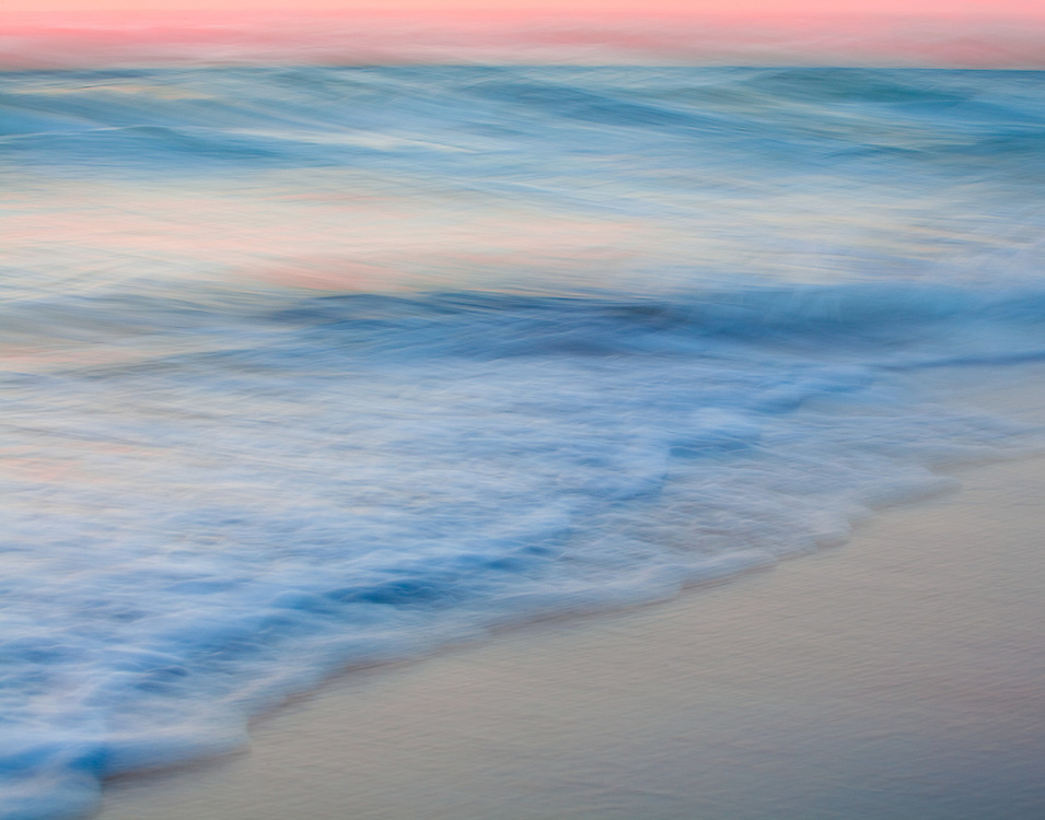 The surf gives the sandy shore a gentle touch