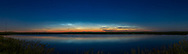 A fine display of noctilucent clouds, or NLCs, or polar mesospheric clouds, reflected in a local prairie pond near home in southern Alberta. The display started with wisps much higher in the north but they faded as the Sun dropped lower, with the display at this extent by the time I reached my spot and took this panorama. <br /> <br /> Leo and Regulus are setting at far left in the west, as is Venus just above the horizon at left. Capella and Auriga are at centre, and circumpolar, while the stars of Perseus at right, rising.<br /> <br /> This is a panorama of 9 segments, at 15&deg; spacings, with the 35mm lens at f/2.8 for 13 second exposures with the Canon 6D MkII at ISO 400. Stitched with Adobe Camera Raw which worked well for this panorama as I shot content at either end to anchor the segments with more foreground content for aiding the stitching. I cropped out the far end content (the roadway) but it served its purpose of helping the stitching. Often with segments with lots of blank content ACR refuses to include segments or stitch at all.