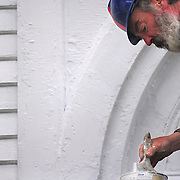 May 14, 2009 -- BATH, Maine.  John Rice of Bath dips a brush into a can of white paint while working on the Winter Street Center in Bath on Thursday afternoon. .The Parish Hall, where Rice and his teammates worked on Thursday, is being weatherized and painted as part of ongoing exterior renovations. .Winter Street Center has been under the management of Sagadahoc Preservation Inc. (SPI) since 1971 and is in a constant state of exterior renovation. SPI recently received a Davis Family Foundation grant and raised matching funds to begin work on the Sanctuary. Work on the steeple and finials was completed last year. .For more information on the Winter Street Center, Sagadahoc Preservation Inc or other local historical buildings contact Elizabeth Knowlton by email : innkeeper@innatbath.com. Photo by Roger S. Duncan.